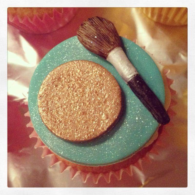A cupcake topped with a brozer base and a makeup brush decoration