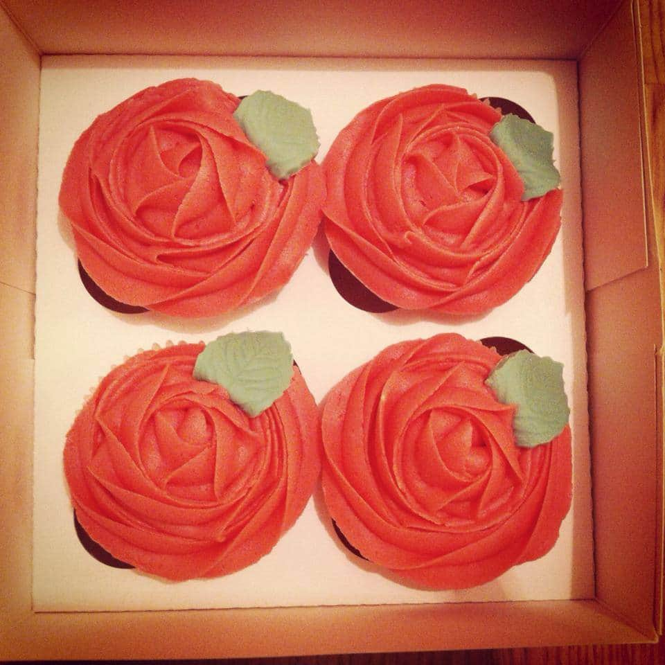 Four cupcakes in a box, decorated as red cupcakes