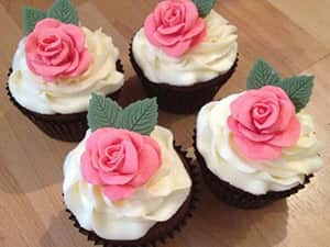 Four cupcakes with white buttercream icing, topped with pink roses made from icing