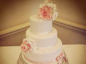 A white, three tier wedding cake decorated with two pink roses