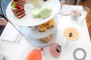 Afternoon tea from above with cocktails on white tablecloth