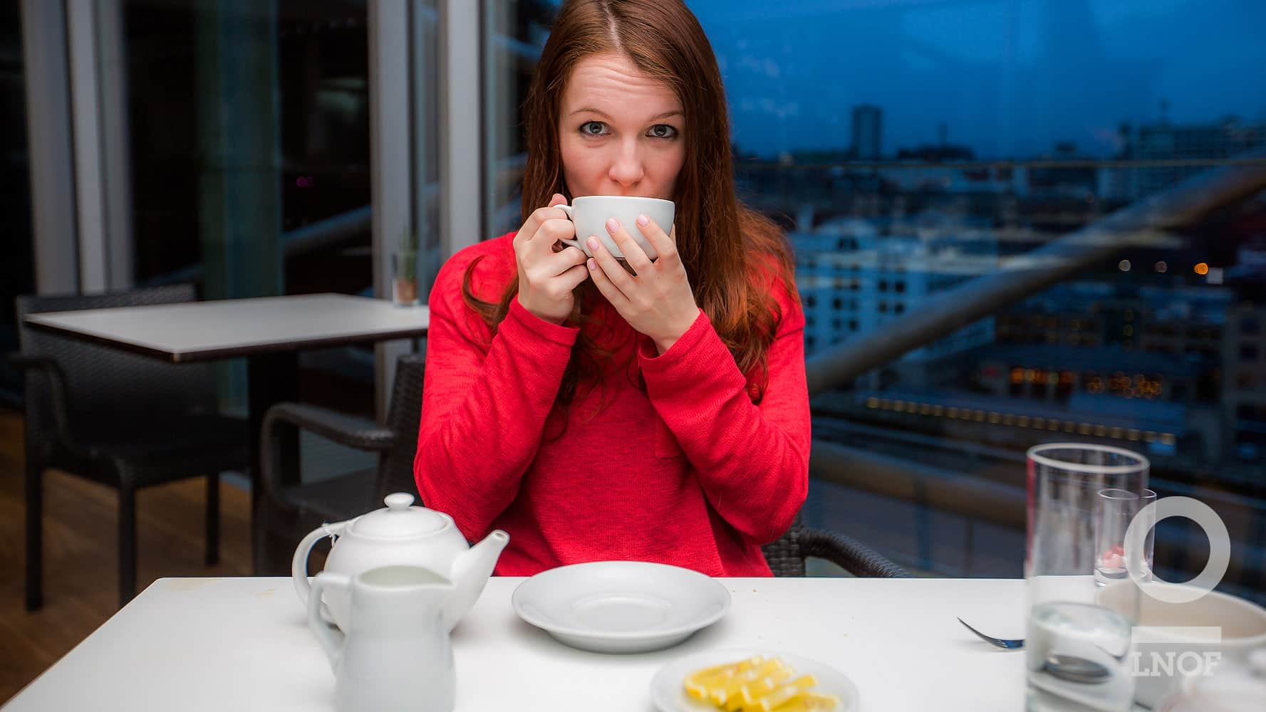 Girl drinking tea in a red jumper