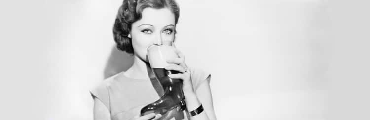 Woman drinking from a boot shaped beer glass