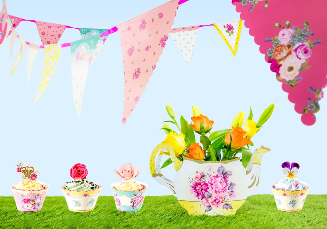 Bunting above cakes on a grass and sky backdrop