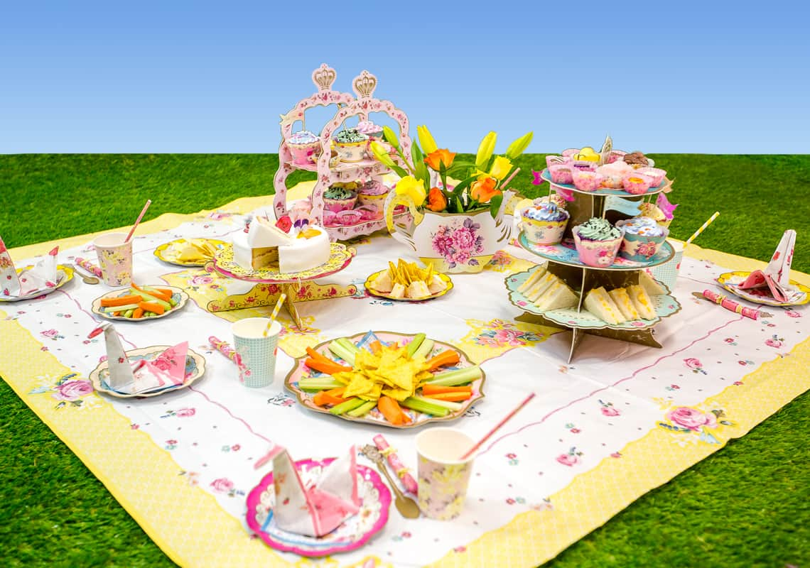 picnic food on a floral mat on fake grass
