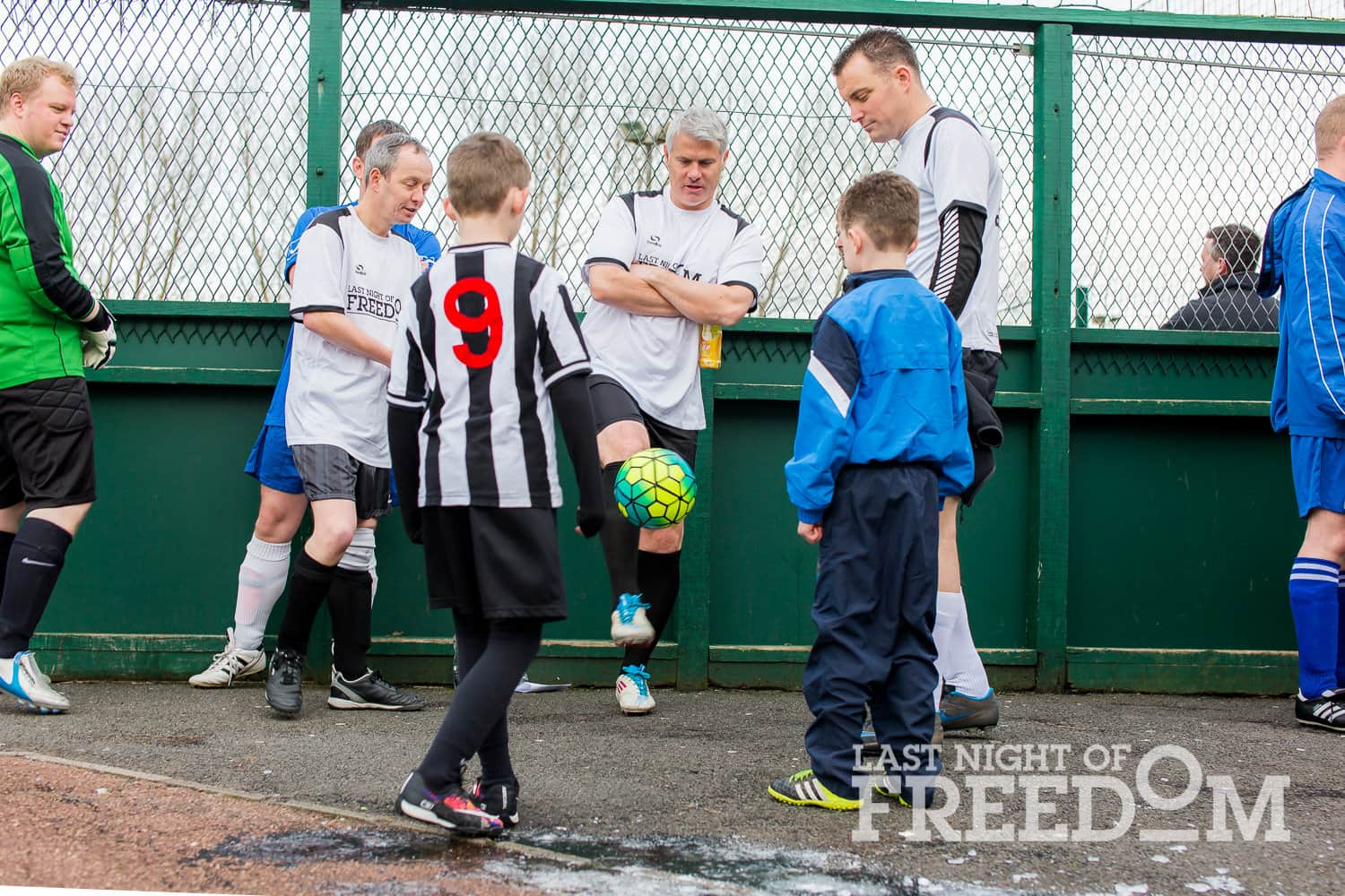 Rob Lee playing football with kids on the edge of the pitch