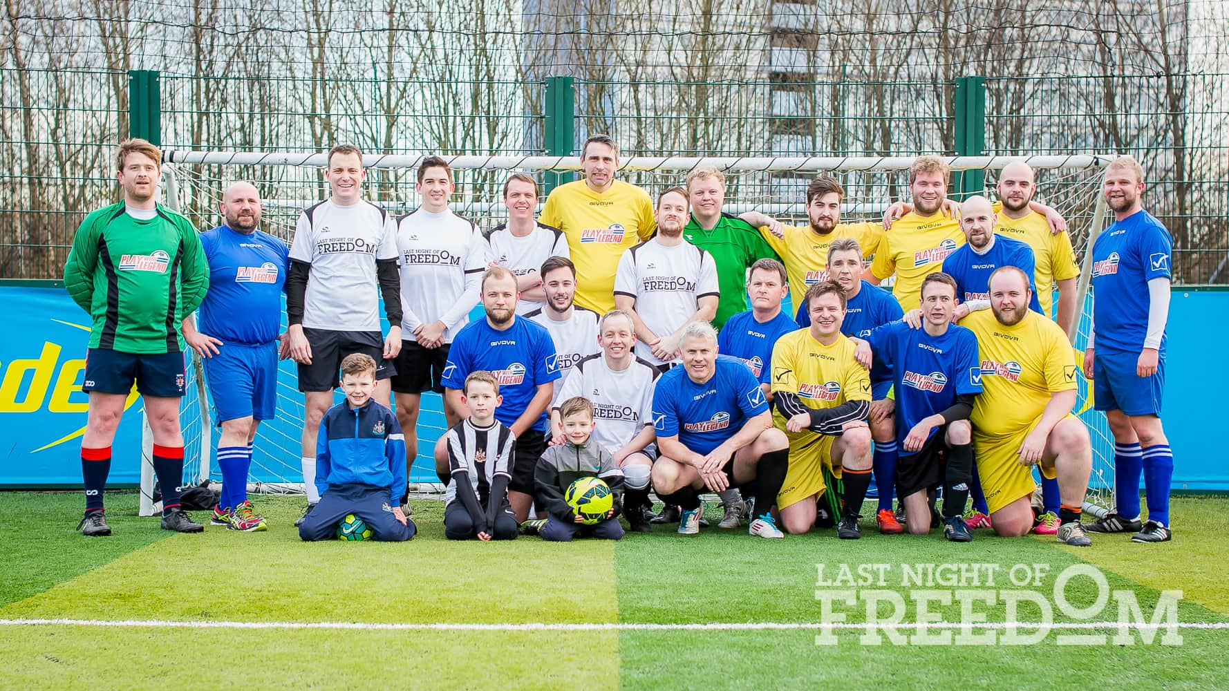 Group of men in football kits posing with former footballer Rob Lee