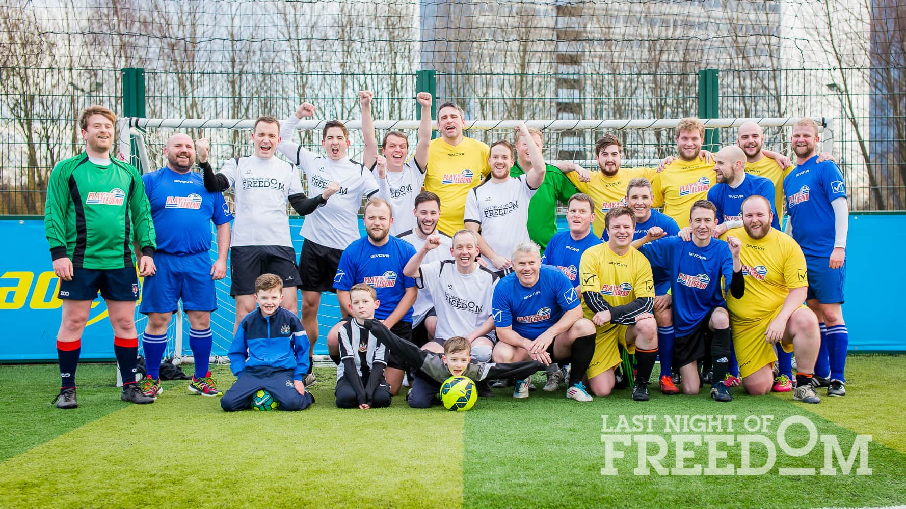 All players in white, blue and yellow kit gather in the goal area for a group photo with Rob Lee