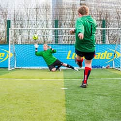 Sales team member Adam scores a penalty against rival goalkeeper Joe