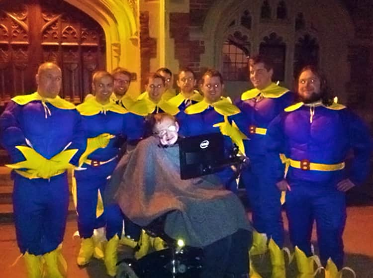 Stephen Hawking posing for a picture with a group of men dressed as Bananaman