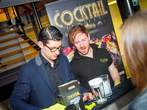 Two men making cocktails behind a pop-up bar with people looking on