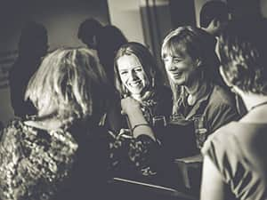 Women laughing at a housewarming party