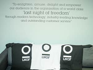 Three T-shirts with LNOF logos printed on, laid against a sofa under the LNOF mission statement