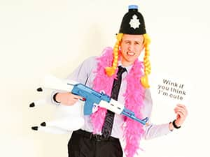 A man holding a fake rifle, wearing a police hat and pink feather boa whilst holding a speech mark card
