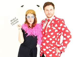 A woman wearing a viking hat and feather boa whilst holding a speech card, posing next to a man in a red Opposuit blazer