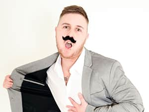 A man posing with a fake moustache on