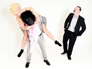 A man wearing a monkey head, giving a man in a women's fatsuit a piggyback whilst another man looks on