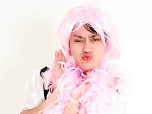 A man in a dress, pink wig and pink feather boa