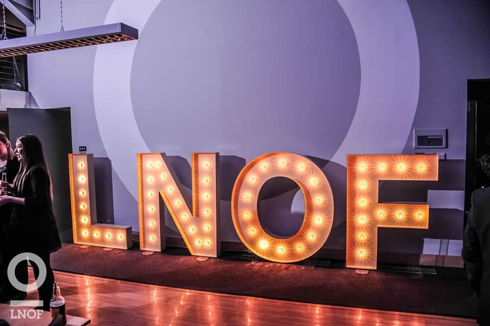 A sign of the word LNOF lit up against a wall, with a woman in the foreground