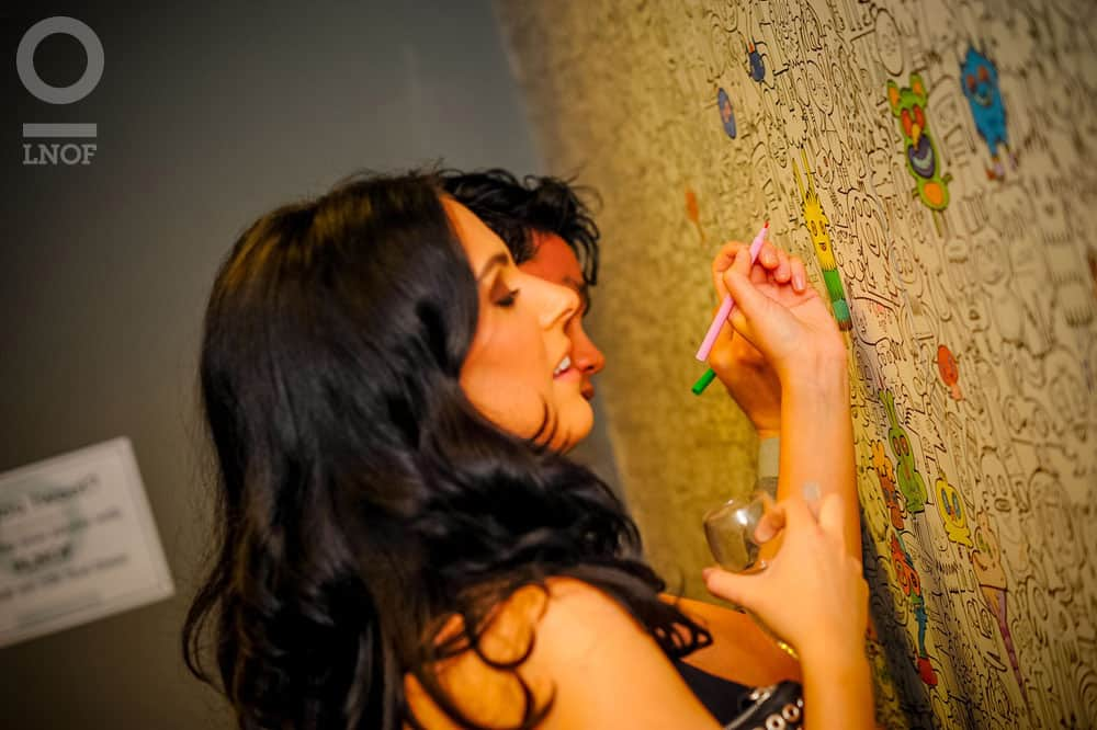 A woman colouring on a wall, with a man in the background