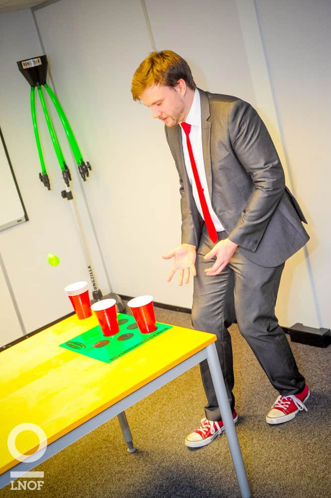 A man in a suit playing beer pong