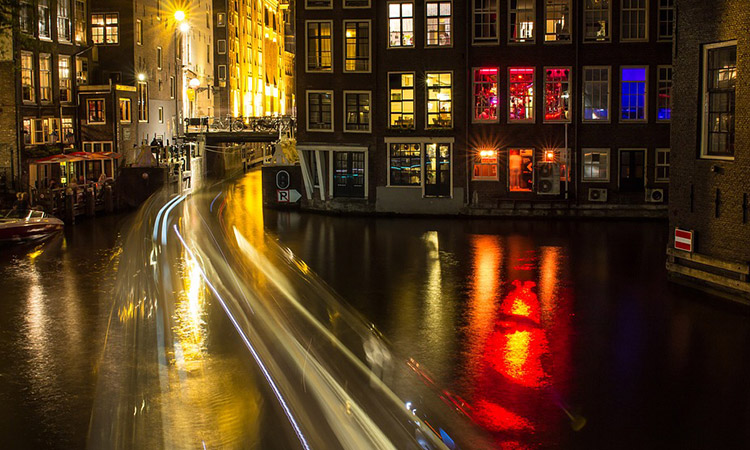 One of the canals in Amsterdam, lit up at night, with buildings in the background