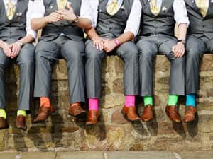 Men sat on a wall in suits flashing their colourfu