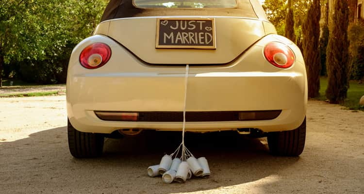 A wedding car with Just Married on the back and cans hanging off the boot