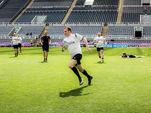The MD running down the pitch with a rugby ball