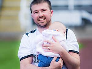 Will with his little baby on the pitch