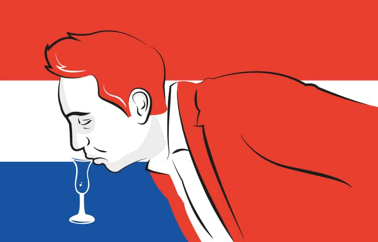 An illustration of a man in a red blazer, bending down over a table to take a sip of his drink