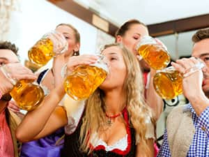 A group of men and women drinking beer from steins