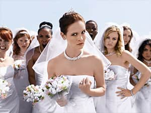 Women in wedding dresses and holding bouquets