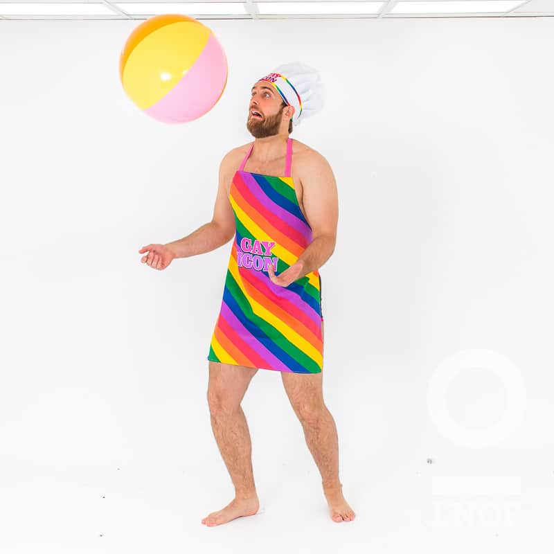 A semi-naked man in a Gay Icon apron and white chef hat, throwing a beach ball in the air