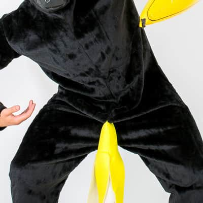 A man posing in a black money costume and holding an inflatable yellow banana under his arm