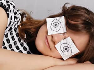 A woman on her side with paper covering her eyes