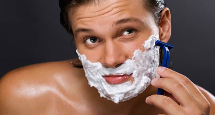 handsome man shaving beard off
