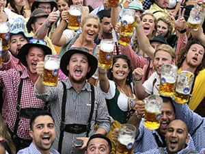 A group of people at a beer festival holding up their steins