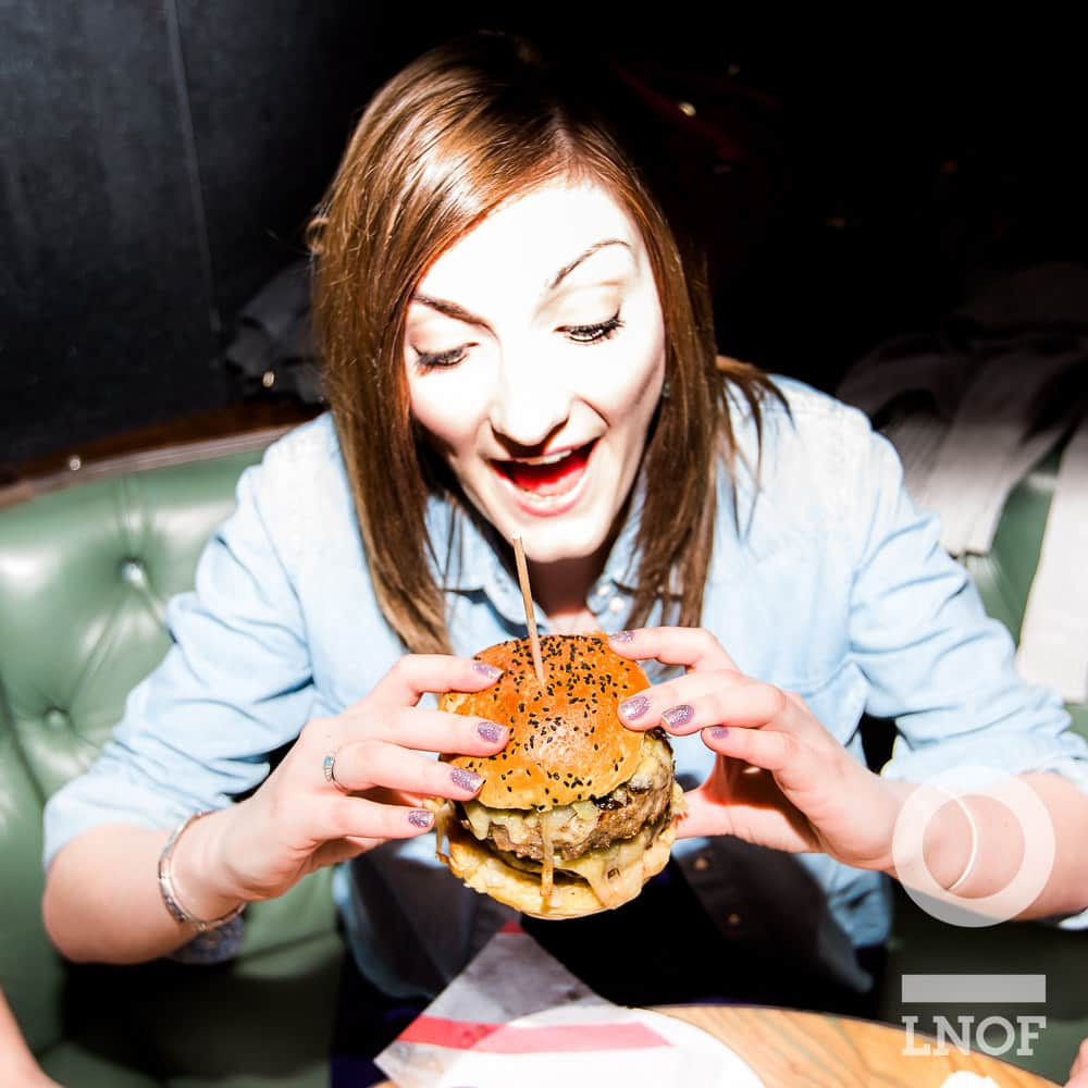 A woman working for LNOF attempting tucking into the dAt Burger at dAt bAr, Newcastle Upon Tyne