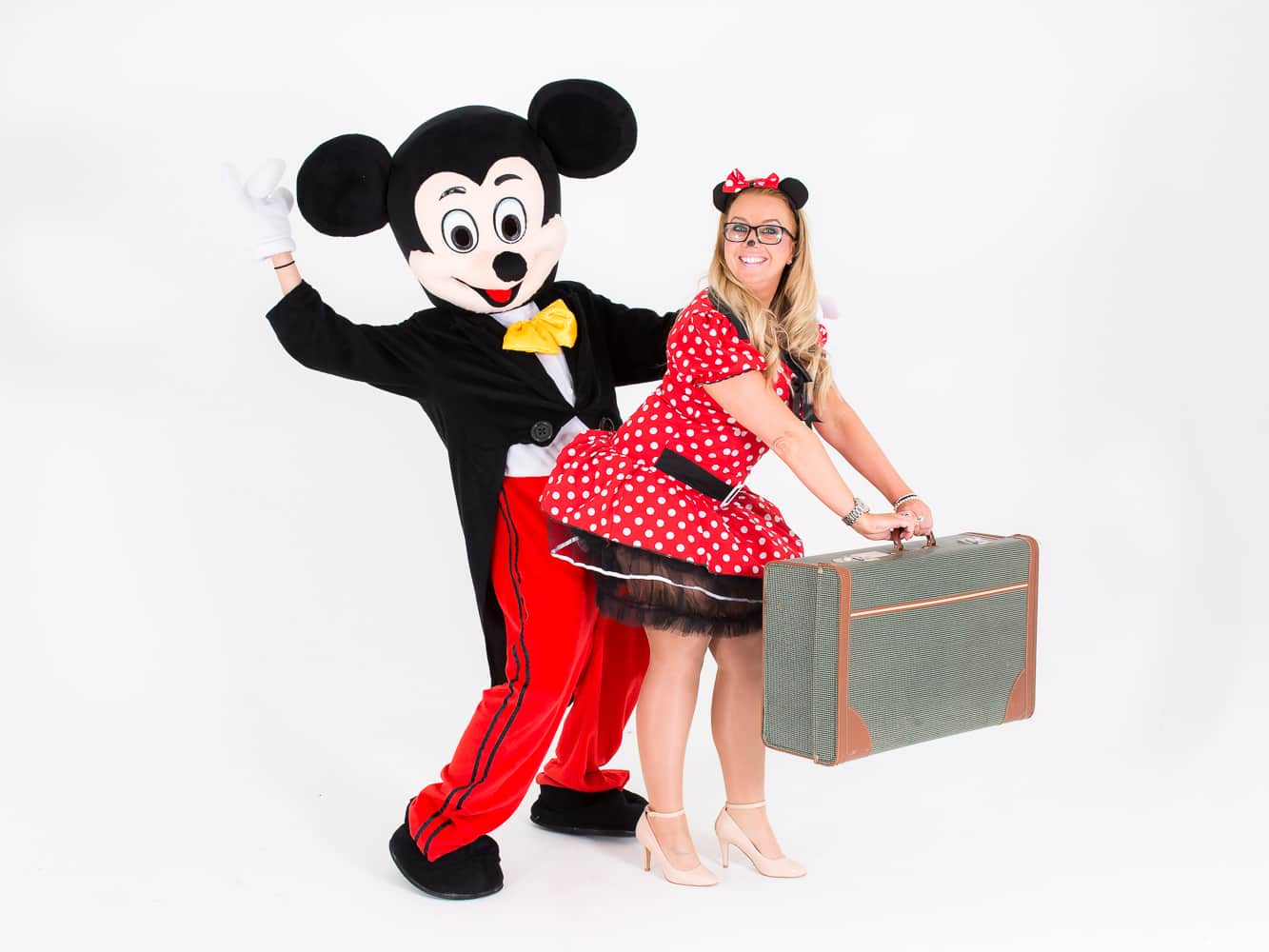 Mickey Mouse and Minnie mouse posing for the camera whilst Minnie holds a suitcase