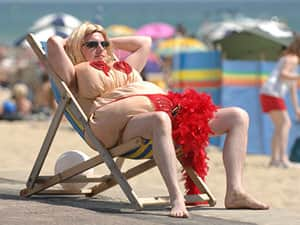 A man in a red fat suit with fake boobs sat in a deck chair