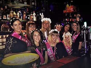 Women on a hen weekend, stood behind a bar and wearing hen party sashes