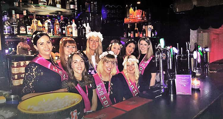 An image of women on a hen weekend behind a bar and posing in their hen party sashes