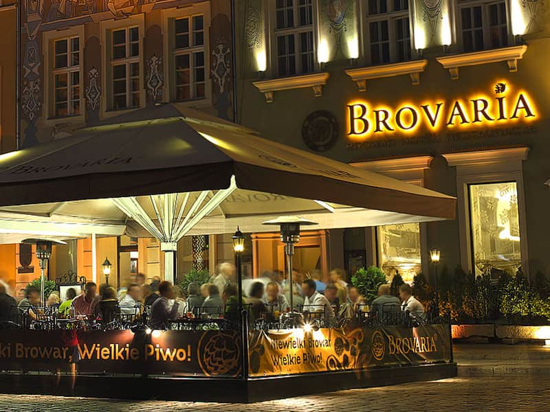 A close up of the Brovaria Hotel with people sitting outside in the restaurant