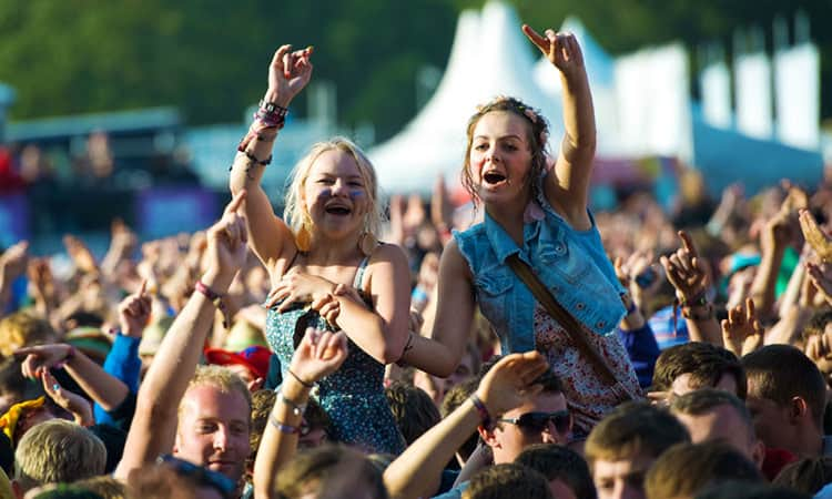 Girls at a festival with their hands in the air