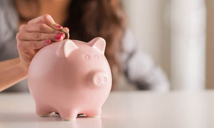 Woman putting money into a piggybank