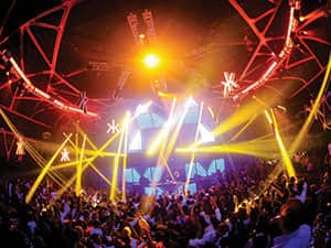People partying in a club with red and yellow lights