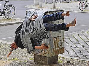 A man gaffa taped to a post in the street with graffiti on him