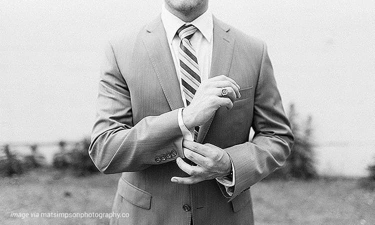 The torso of a man wearing a grey suit, adjusting his cuff
