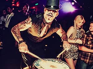 A man in a top hat and waistcoat playing the drums in a busy club